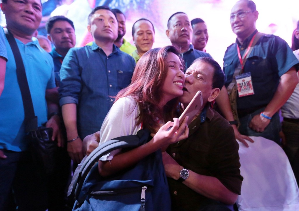 Presidential aspirant Rodrigo Duterte kisses a woman during his proclamation rally. GRIG MONTEGRANDE/PHILIPPINE DAILY INQUIRER